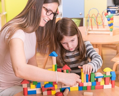 Kindergarten Teacher and Kid Playing with Wooden Building Blocks