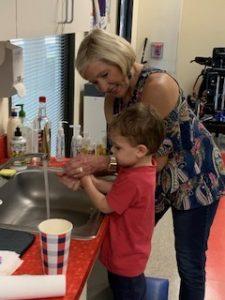 therapist hand washing with child